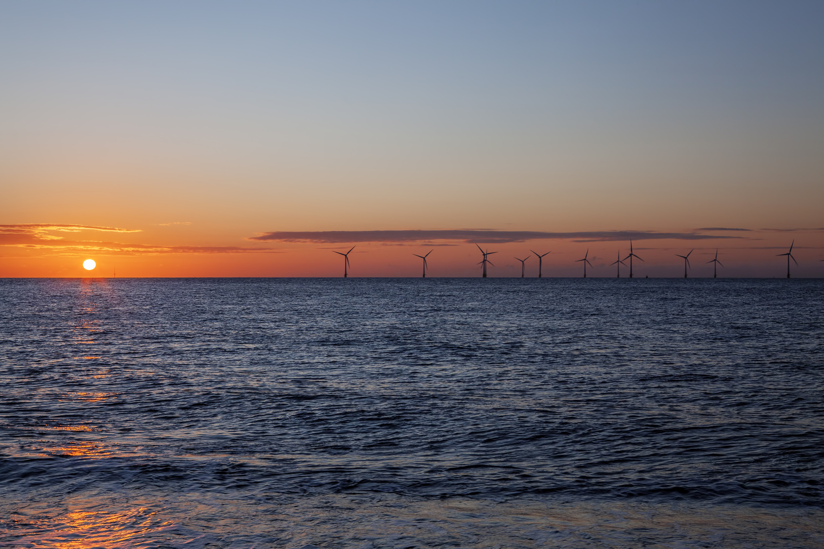 Renewable energy. Offshore wind farm on the horizon at sunrise. © Ian Dyball | Fotolia